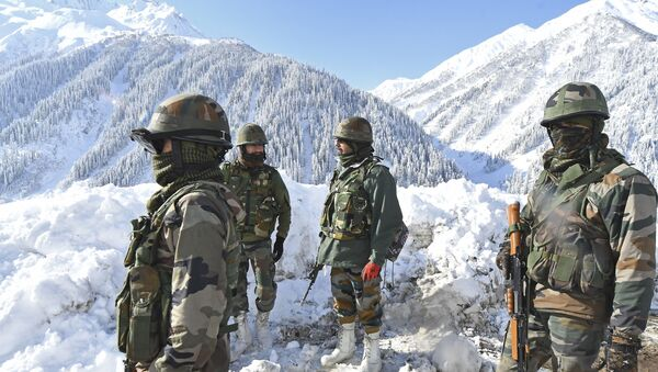 Indian army soldiers on 28 February 2021 stand on a snow-covered road near the Zoji La mountain pass that connects Srinagar to the union territory of Ladakh, bordering China. - Sputnik International