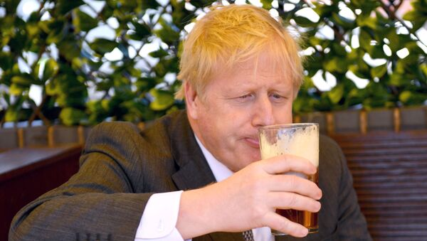 Prime Minister Boris Johnson sips a pint in the beer garden during a visit to The Mount Tavern Pub and Restaurant on the local election campaign trail in Wolverhampton, West Midlands, 19 April 2021 - Sputnik International