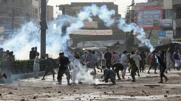 Supporters of the Tehreek-e-Labaik Pakistan (TLP) Islamist political party throwback tear gas canisters fired by police during a protest against the arrest of their leader in Lahore, Pakistan April 13, 2021. - Sputnik International