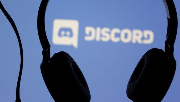 Headphones are seen in front of displayed Discord app logo in this illustration taken March 29, 2021.  - Sputnik International