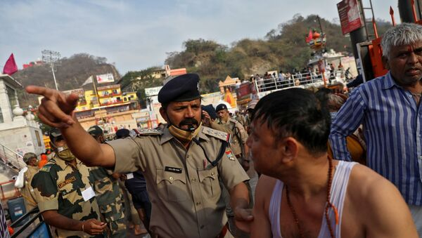 A police officer asks a devotee to leave after he took a holy dip in the waters of river Ganges during Kumbh Mela, or the Pitcher Festival, amidst the spread of the coronavirus disease (COVID-19), in Haridwar, India, April 12, 2021.  - Sputnik International