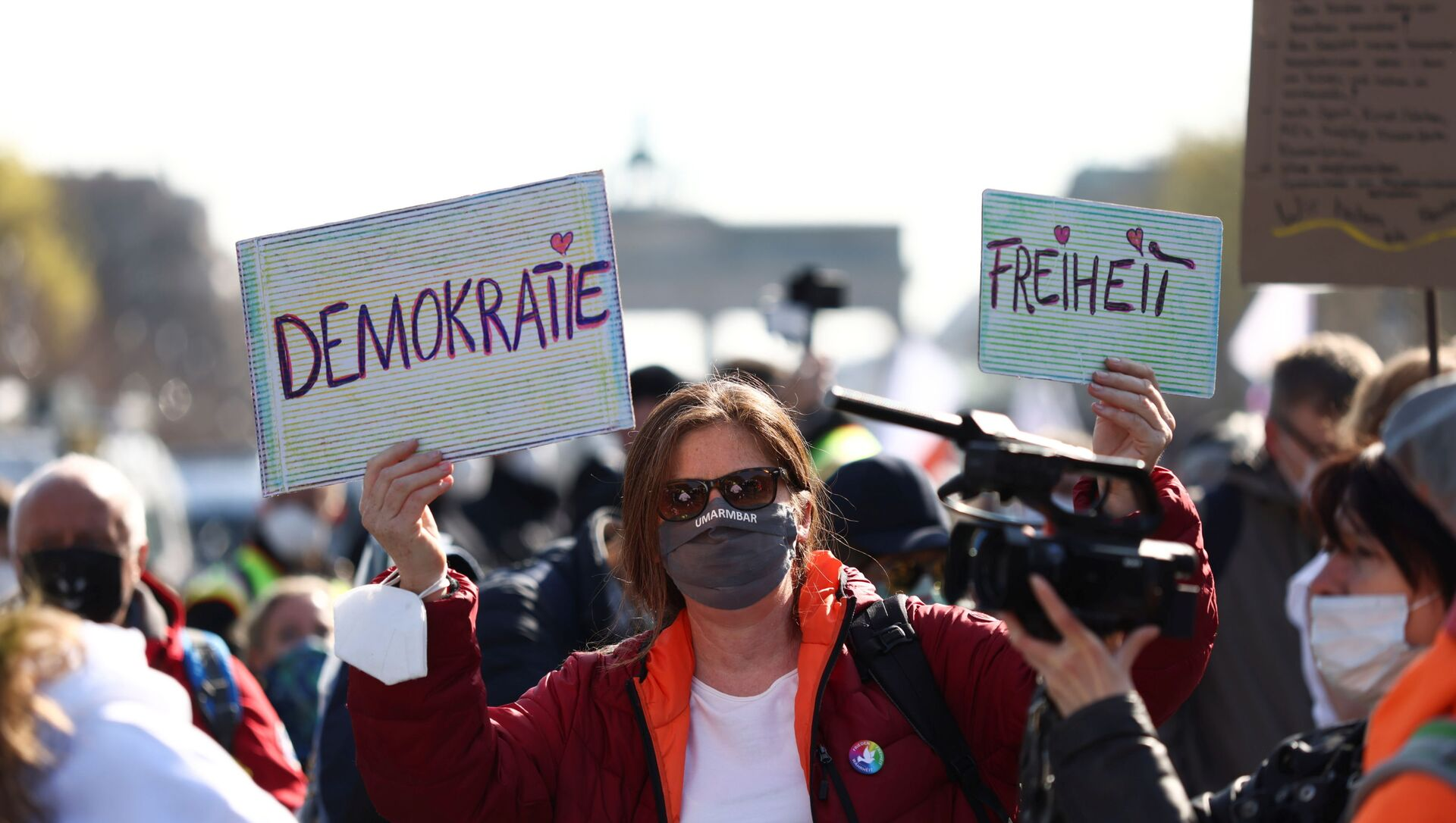 A demonstrator holds up signs reading democracy and freedom during a protest against the government measures to curb the spread of the coronavirus disease (COVID-19), on the day of discussion in the lower house of parliament Bundestag regarding additions for the Infection Protection Act, in Berlin, Germany April 21, 2021 - Sputnik International, 1920, 01.08.2021