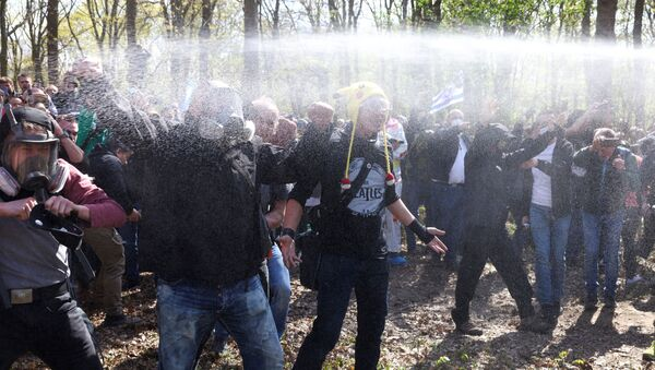 Demonstrators are sprayed with pepper spray during a protest against the government measures to curb the spread of the coronavirus disease (COVID-19), on the day of discussion in the lower house of parliament Bundestag regarding additions for the Infection Protection Act, in Berlin, Germany April 21, 2021 - Sputnik International