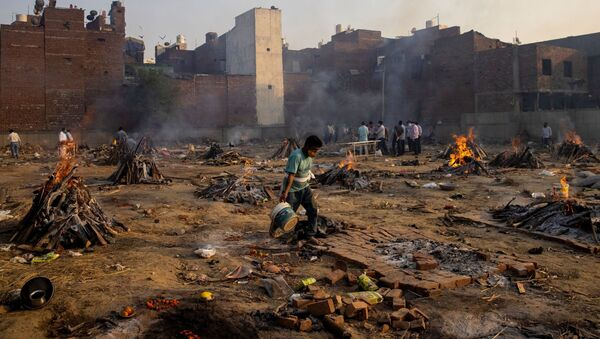 Funeral pyres of people, who died due to the coronavirus disease (COVID-19), are pictured at a crematorium ground in New Delhi, India, April 22, 2021 - Sputnik International
