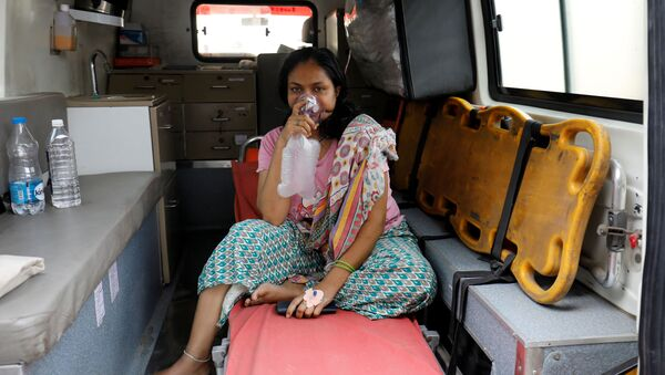 A patient with breathing problems wears an oxygen mask as she waits inside an ambulance in a queue to enter a COVID-19 hospital, amidst the coronavirus disease pandemic, Ahmedabad, India, April 14, 2021 - Sputnik International