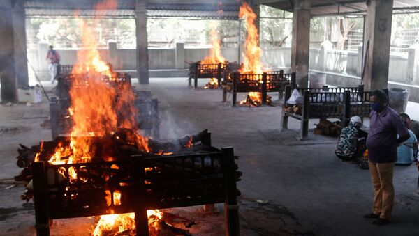 The relation of a victim of the coronavirus disease (COVID-19), who died after a hospital caught fire, looks on as funeral pyres burn inside a crematorium in Virar, on the outskirts of Mumbai, India, 23 April 2021. - Sputnik International