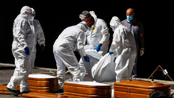 Rescuers from the Spanish Coast Guard place one of the recovered bodies of four deceased migrants into a coffin at the port of La Restinga, on the Canary Island of El Hierro - Sputnik International