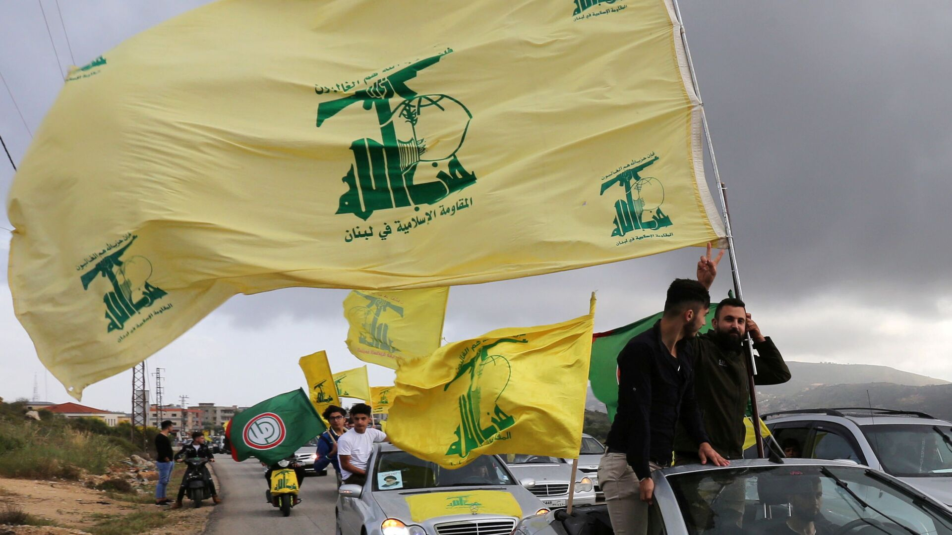 FILE PHOTO: A supporter of Lebanon's Hezbollah gestures as he holds a Hezbollah flag in Marjayoun, Lebanon May 7, 2018. - Sputnik International, 1920, 17.09.2021
