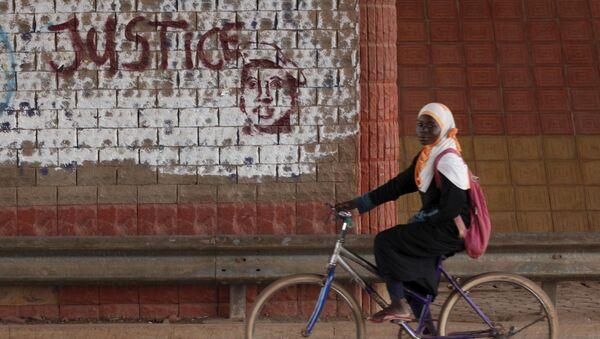 A girl rides a bicycle past graffiti reading Justice with a picture of slain ex-President Thomas Sankara in Ouagadougou, Burkina Faso, December 4, 2015. - Sputnik International