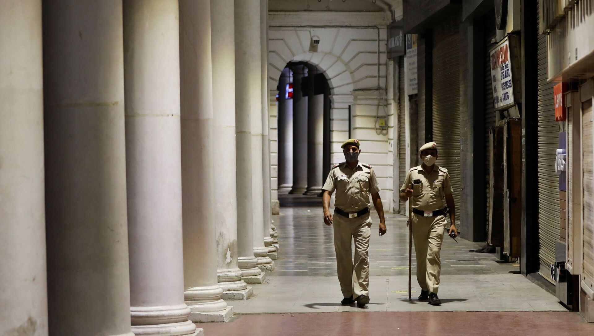 Police officers patrol in front of closed shops at a market area during a curfew to limit the spread of the coronavirus disease (COVID-19), in New Delhi, India, 6 April 2021. - Sputnik International, 1920, 01.05.2021