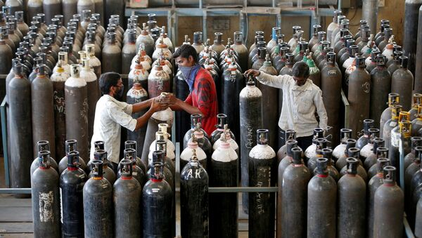 People carry oxygen cylinders after refilling them in a factory, amidst the spread of the coronavirus disease (COVID-19) in Ahmedabad, India, April 25, 2021 - Sputnik International