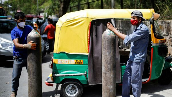 Rickshaw drivers hold oxygen cylinders outside a private refilling station, amid the coronavirus disease (COVID-19) outbreak, in New Delhi, India, April 19, 2021 - Sputnik International