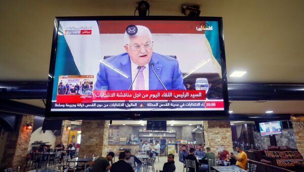 A screen displaying a live broadcast of Palestinian President Mahmoud Abbas's speech during a meeting to discuss upcoming elections, is seen in a coffee shop in Ramallah in the Israeli-occupied West Bank April 29, 2021. - Sputnik International