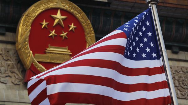 In this Nov. 9, 2017, file photo, an American flag is flown next to the Chinese national emblem during a welcome ceremony for visiting U.S. President Donald Trump outside the Great Hall of the People in Beijing.  - Sputnik International