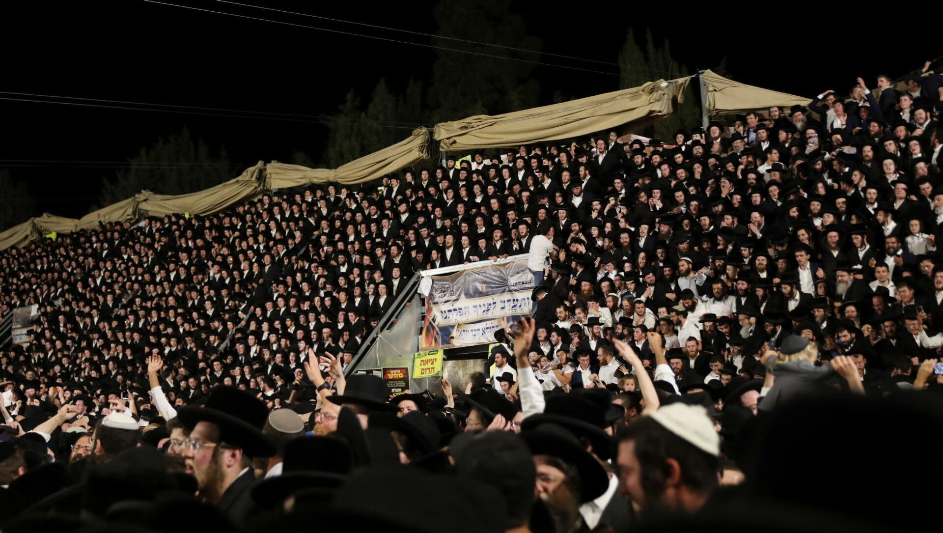 Jewish worshippers sing and dance as they stand on tribunes at the Lag B'Omer event in Mount Meron, northern Israel, April 29, 2021. - Sputnik International, 1920, 29.04.2021