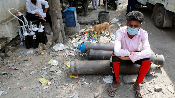 FILE PHOTO: Sumit Kumar, 28, sits on an oxygen cylinder as he waits outside a factory to get it refilled, amidst the spread of the coronavirus disease (COVID-19) in New Delhi, India - Sputnik International