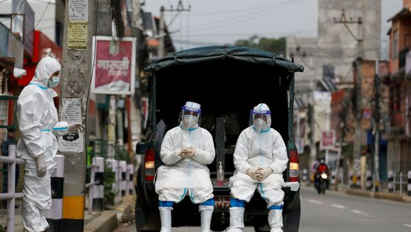 Members of Nepal army personnel wearing personal protective equipment (PPE) rest on a vehicle as they wait to transport a body of a person who died from coronavirus disease (COVID-19) to the crematorium, while Nepal is overwhelmed by a COVID-19 surge as India's outbreak spreads across South Asia, in Kathmandu, Nepal May 5, 2021.  - Sputnik International