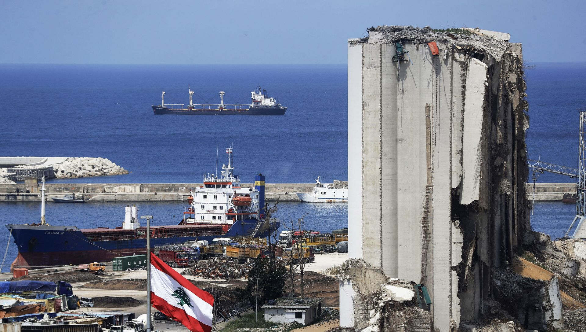 A picture shows a view of the damaged grain silos at the port of the Lebanese capital Beirut, on April 9, 2021, still reeling from the destruction due to a catastrophic blast in a harbour storage unit last August that killed more than 200 people and damaged swathes of the capital, with the Togo-flagged Fatima M bulk carrier ship moored nearby.  - Sputnik International, 1920, 02.08.2021