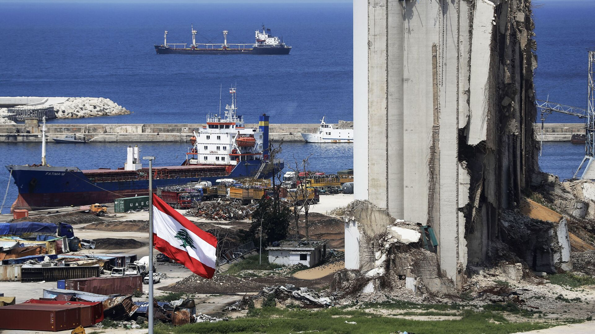A picture shows a view of the damaged grain silos at the port of the Lebanese capital Beirut, on April 9, 2021, still reeling from the destruction due to a catastrophic blast in a harbour storage unit last August that killed more than 200 people and damaged swathes of the capital, with the Togo-flagged Fatima M bulk carrier ship moored nearby.  - Sputnik International, 1920, 03.09.2021