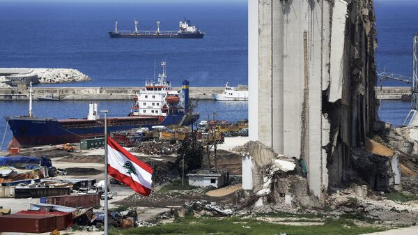 A picture shows a view of the damaged grain silos at the port of the Lebanese capital Beirut, on April 9, 2021, still reeling from the destruction due to a catastrophic blast in a harbour storage unit last August that killed more than 200 people and damaged swathes of the capital, with the Togo-flagged Fatima M bulk carrier ship moored nearby.  - Sputnik International