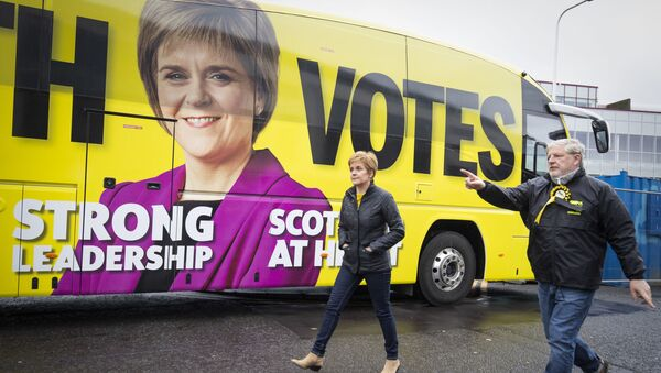 Scotland's First Minister and leader of the Scottish National Party (SNP), Nicola Sturgeon (R) walks past the campaign battle bus with SNP candidate Angus Robertson during a campaign visit to LOVE Gorgie Farm in Edinburgh, Scotland on May 4, 2021, ahead of the upcoming Scottish Parliament election which is to be held on May 6, 2021. - Sputnik International