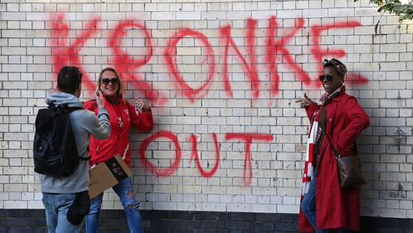 Two fans have their photograph taken beside a Kronke Out message sprayed on a wall as supporters protest against Arsenal's US owner Stan Kroenke, outside English Premier League club Arsenal's Emirates stadium in London on 23 April 2021, ahead of their game against Everton. - Sputnik International