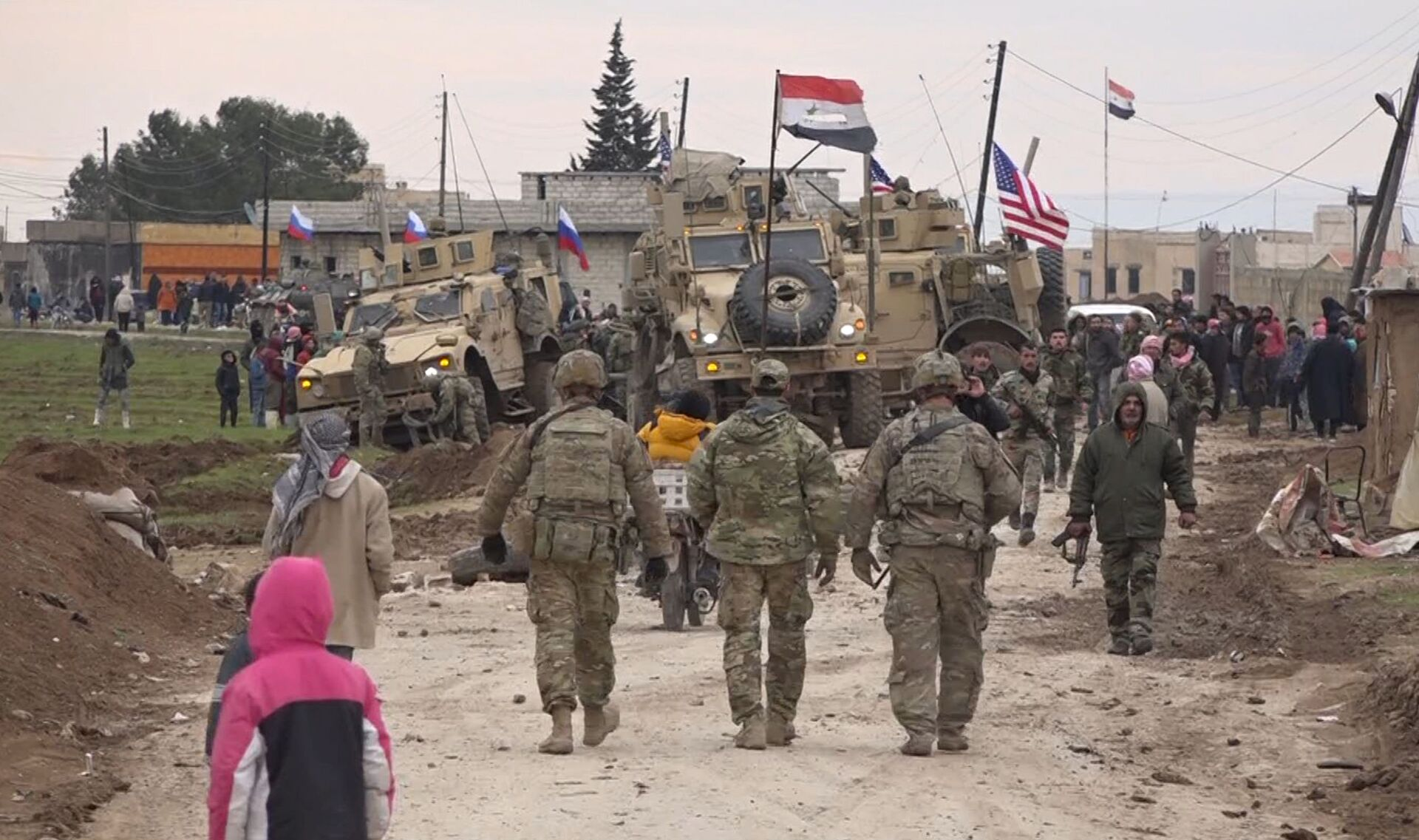 In this frame grab from video, Russian, Syrian and others gather next to an American military convoy stuck in the village of Khirbet Ammu, east of Qamishli city, Syria, Wednesday, Feb. 12, 2020. The Syrian official news agency SANA, said Wednesday, that locals had gathered at an army checkpoint, pelting the U.S. convoy with stones and taking down a U.S. flag flying on a vehicle when troops fired with live ammunition and smoke bombs. (AP Photo) - Sputnik International, 1920, 07.09.2021
