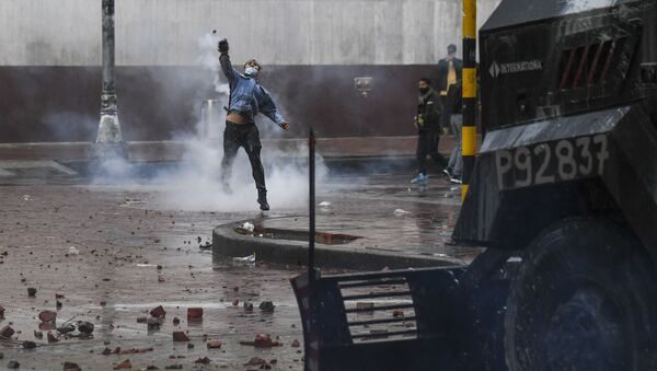 A demonstrator throws a stone at riot police vehicle during a protest against President Ivan Duque's government at the Bolivar square in Bogota on May 5, 2021. - Thousands of people returned to the streets of Colombia on Wednesday in rejection of the government of Ivan Duque, who has completed a week of pressure with demonstrations that turned violent in some cities and left some twenty people dead.  - Sputnik International