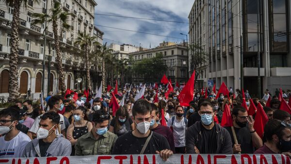 Demonstrators wearing protective face masks against the coronavirus, Covid-19, and members of the Greek Labour Union (PAME) protest during a strike against the new Labour law, in central Athens on May 6, 2021. - Sputnik International