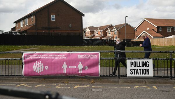 People walk past banners for a polling station in Hartlepool, County Durham on 6 May 2021, as voters cast their ballots in local elections. - Sputnik International