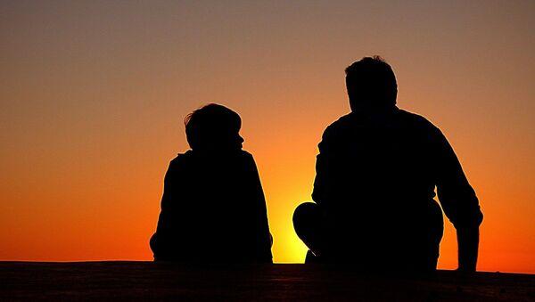 A father and son sit together - Sputnik International