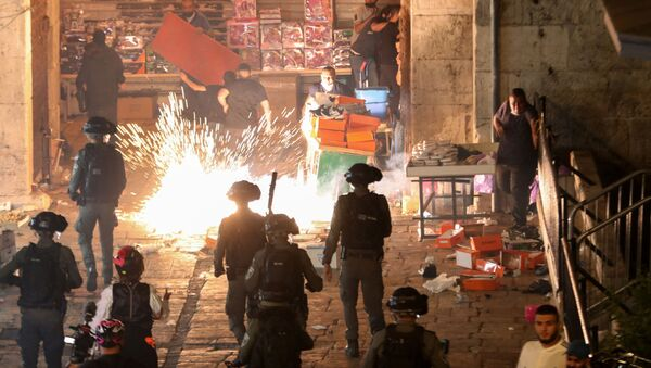 Palestinians react as Israeli police fire a stun grenade during clashes at Damascus Gate on Laylat al-Qadr during the holy month of Ramadan, in Jerusalem's Old City, May 9, 2021 - Sputnik International