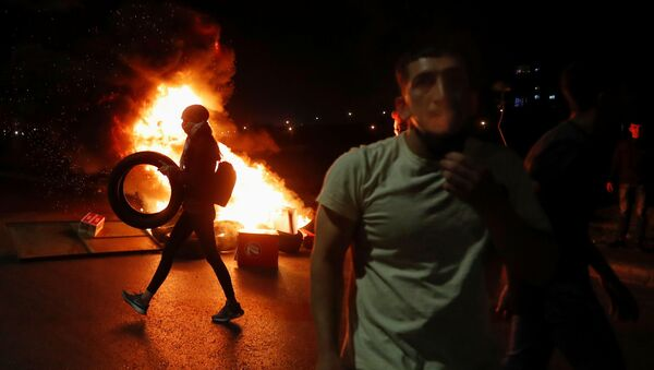 A Palestinian woman demonstrator carries a tire as she walks past a burning barricade during an anti-Israel protest over tension in Jerusalem, near the Jewish settlement of Beit El near Ramallah, in the Israeli-occupied West Bank May 9, 2021 - Sputnik International