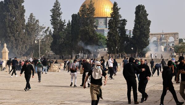 Palestinians run for cover from tear gas fired by Israeli security forces at Jerusalem's Al-Aqsa mosque compound on May 10, 2021, ahead of a planned march to commemorate Israel's takeover of Jerusalem in the 1967 Six-Day War.  - Sputnik International