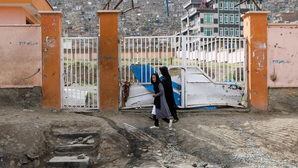 A woman with a girl walks past the site of a car bomb blast that targeted schoolgirls in Kabul, Afghanistan May 10, 2021.  - Sputnik International