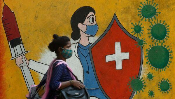 A woman walks past a graffiti on a street, amidst the spread of the coronavirus disease (COVID-19) in Mumbai, India, May 10, 2021 - Sputnik International