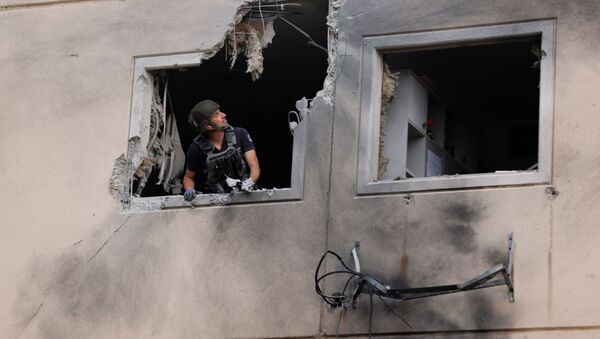 An Israeli police bomb disposal expert looks out from the window of a residential building that was damaged after it was hit by a rocket launched from the Gaza Strip, in Ashkelon, southern Israel May 11, 2021.  - Sputnik International