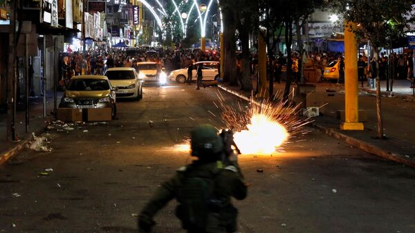 A stun grenade fired by Israeli forces explodes as Palestinians take part in an anti-Israel protest amid a flare-up of Israeli-Palestinian violence, in Hebron in the Israeli-occupied West Bank May 11, 2021. - Sputnik International