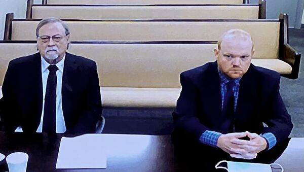 In this image made from video, from left, father and son, Gregory and Travis McMichael, accused in the shooting death of Ahmaud Arbery in Georgia on Feb. 2020, listen via closed circuit tv in the Glynn County Detention center in Brunswick, Ga., on Thursday, Nov. 12, as lawyers argue for bond to be set at the Glynn County courthouse.  - Sputnik International