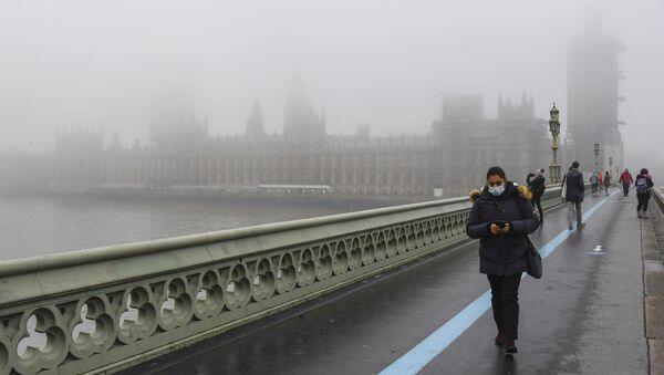 People wearing face masks, walk over Westminster Bridge with the Houses of Parliament shrouded by fog, in London, Tuesday, Dec. 8, 2020 - Sputnik International