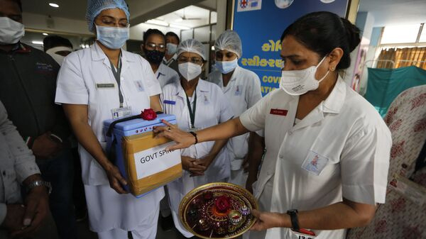 A nurse, right, performs rituals on a box containing COVID-19 vaccines upon its arrival at a government hospital in Ahmedabad, India, 16 January 2021 - Sputnik International