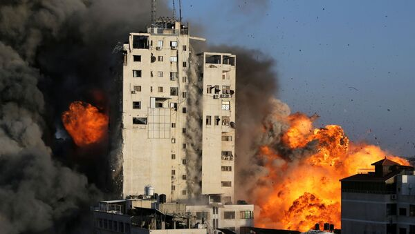 Smoke and flames rise from a tower building as it is destroyed by Israeli air strikes amid a flare-up of Israeli-Palestinian violence, in Gaza City May 12, 2021. - Sputnik International