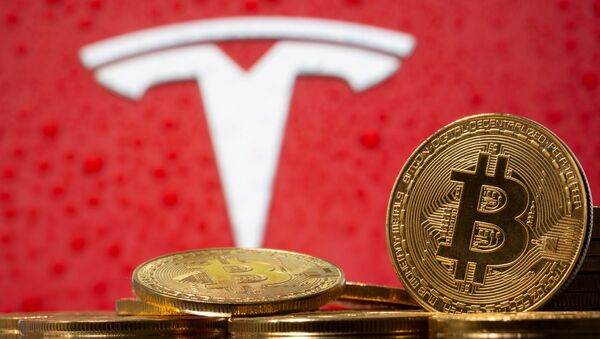 Representations of virtual currency Bitcoin are seen in front of Tesla logo in this illustration taken, February 9, 2021.  - Sputnik International