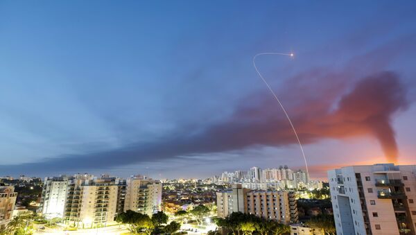 A streak of light is seen as Israel's Iron Dome anti-missile system intercepts rockets launched from the Gaza Strip towards Israel, as seen from Ashkelon, Israel May 12, 2021. - Sputnik International