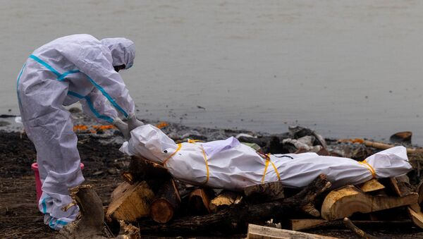 A man wearing a protective suit touches the body of his relative, who died from the coronavirus disease (COVID-19), before his cremation on the banks of the river Ganges at Garhmukteshwar in the northern state of Uttar Pradesh, India, May 6, 2021. - Sputnik International
