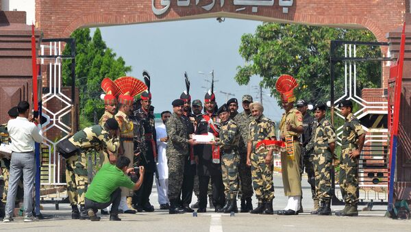 Indian Border Security Force (BSF) commandant Sudeep (centre R) presents sweets to Pakistani Wing Commander Bilal (centre L) on the occasion of the Eid al-Adha festival at the India-Pakistan Wagah border post on September 2, 2017 - Sputnik International