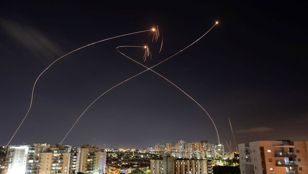 Streaks of light are seen as Israel's Iron Dome anti-missile system intercept rockets launched from the Gaza Strip towards Israel, as seen from Ashkelon, Israel May 13, 2021. - Sputnik International