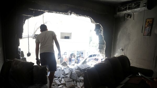 A man stands atop rubble as he surveys the damage after a rocket launched overnight from the Gaza Strip hit a residential building in Petah Tikva, Israel May 13, 2021 - Sputnik International