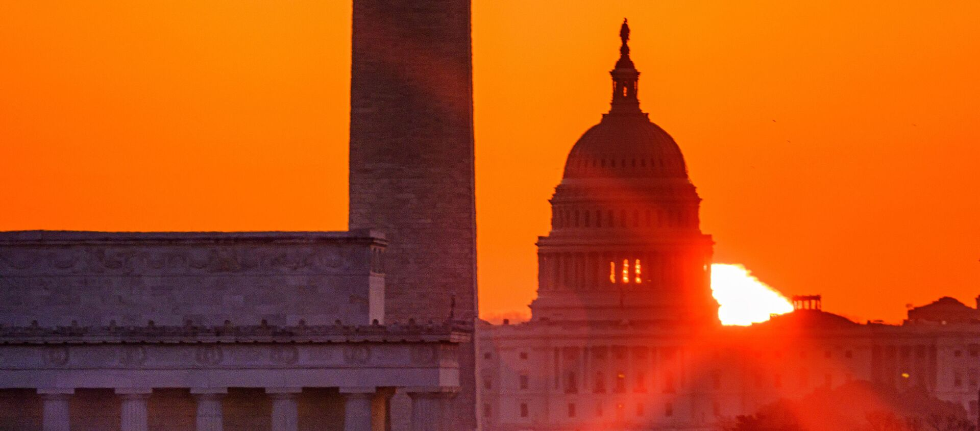 The sun flares through the camera lens as it rises behind the U.S. Capitol building, Washington Monument and the Lincoln Memorial, Monday, March 22, 2021, in Washington. - Sputnik International, 1920, 28.05.2021