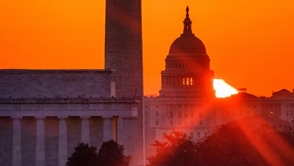 The sun flares through the camera lens as it rises behind the U.S. Capitol building, Washington Monument and the Lincoln Memorial, Monday, March 22, 2021, in Washington. - Sputnik International